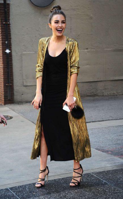 Chica usando un vestido de color negro con un ensamble dorado y bolsa clutch de terciopelo