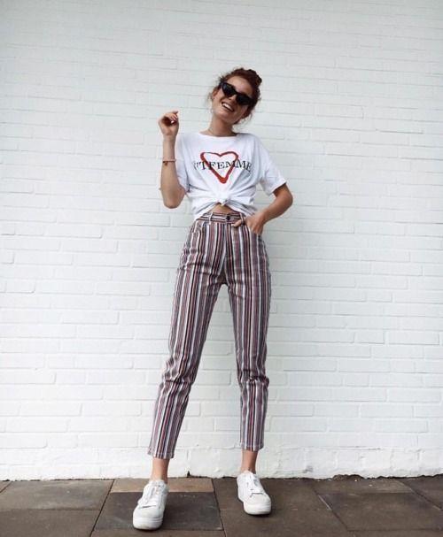 Chica recargada en una pared usando pantalones de vestir a rayas posando para una foto