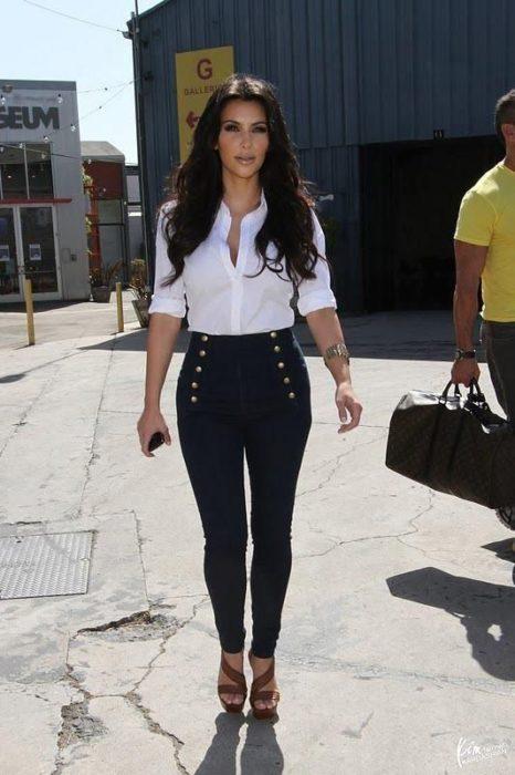 Kim Kardashian usando pantalón de tiro alto en tono negro con botones a los costados