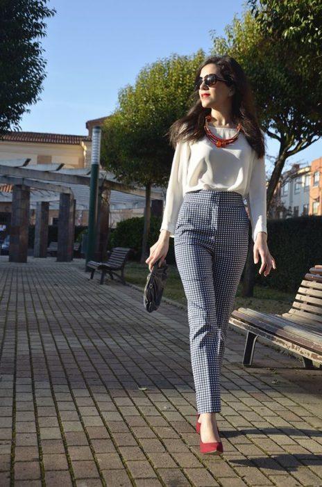 Chica modelando por la plaza usando pantalón de tico alto a cuadros y blusa blanca