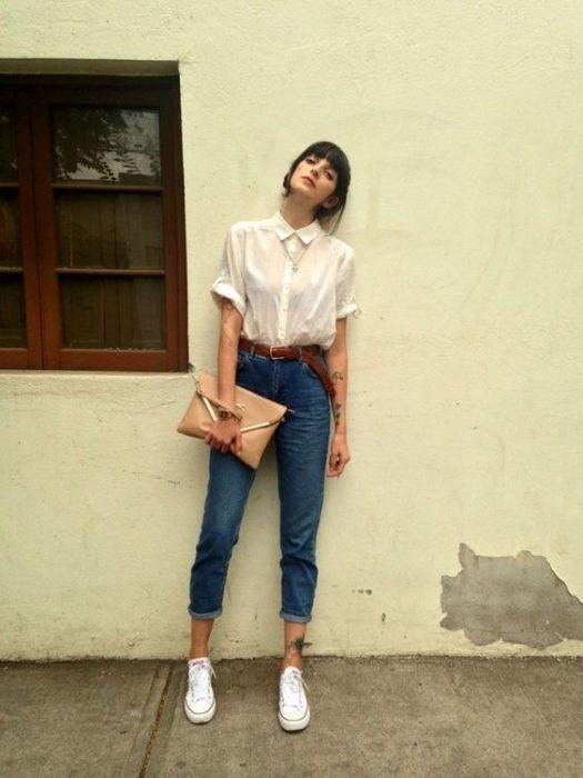 Chica recargada en una pared sosteniendo una cartera y mirando hacia arriba para ser fotografiada
