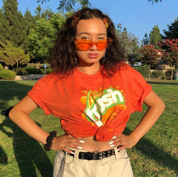 Chica con camiseta naranja, pantalón crema, lentes naranja transparente y broches en forma de flores
