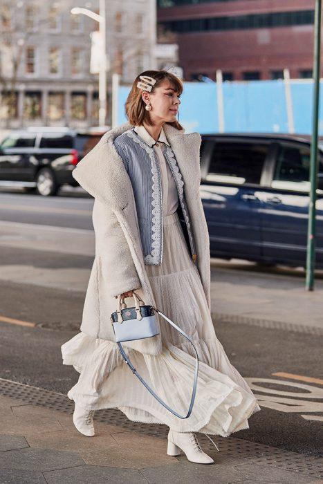 Chica caminando por la calle con vestido blanco de lana, saco, bolso en mano y un par de broches gigantes sobre su cabeza