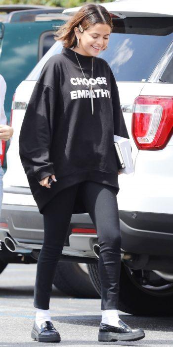 La cantante Selena Gomez caminando por la calle, luciendo unos pantalones negros, sudadera negra holgada y un broche sobre su cabello