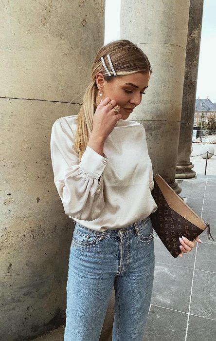 Chica rubia con blusa blanca, jeans de mezclilla y una coleta con dos broches de perlas