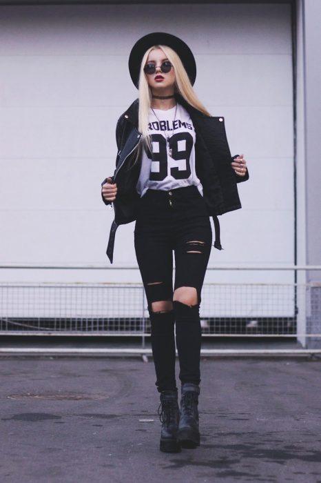 Chica modelando unos jeans negros rotos, camisa blanca con estampado, botas rockeras, sombrero bohemio y una chamarra de piel