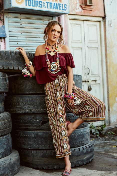 Chica en sesión fotográfica con pantalón con estampado holgado, blusa guinda holgada y gran variedad de accesorios estilo bohemio