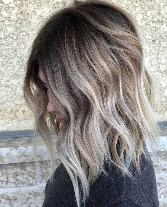 Chica de perfil mirando hacia abajo para mostrar su cabello teñido