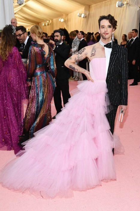 Michael Urie usando un vestido de gasa de color rosa a la mitad de su cuerpo y en la otra un traje de líneas junto con un bolso de mano