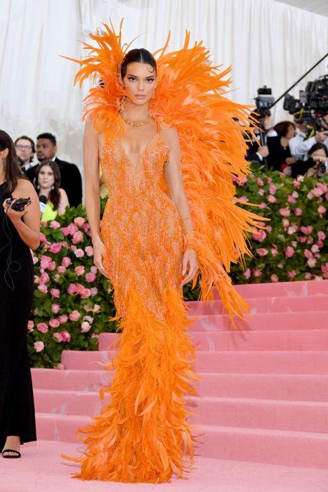 Kendall Jenner usando un vestido de color naranja entallado y cubierto de plumas durante la Gala MET