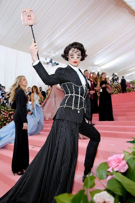 Ezra Miller usando un traje de rayas verticales con un corsaje de pedrería. Como accesorios una mascara y un maquillaje con siete ojos en su rostro
