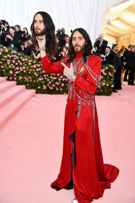 Jared Leto en la Gala MET usando un abrigo largo y rojo mientras sostiene una cabeza similar a su rostro