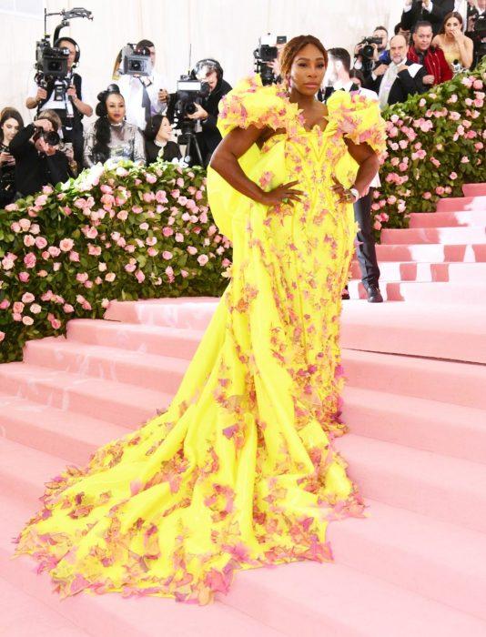 Serena Williams posando en la alfombra rosa del MET Gala. Usa un vestido amarillo con aplicaciones de flores en color rosa