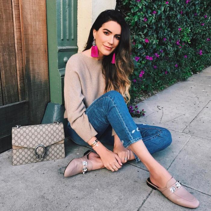 Chica sentada afuera de su casa mostrando su bolsa y sus zapatos mocasines de color rosa