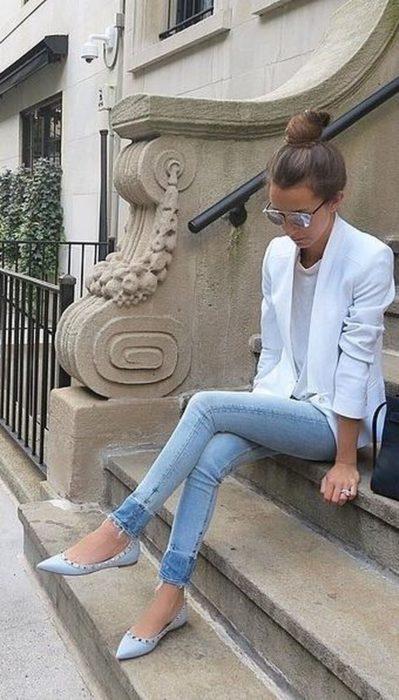 Chica sentada en unas escaleras de la calle admirando sus zapatos color azul