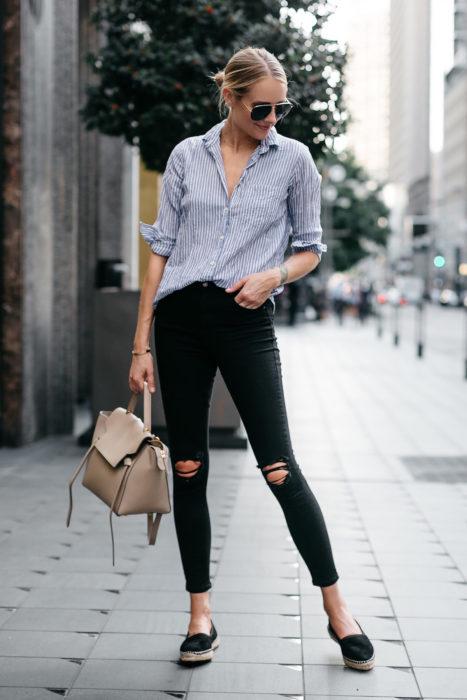 Chica parada en medio de la calle mostrando sus zapatos flats estilo alpargatas de tacón bajo