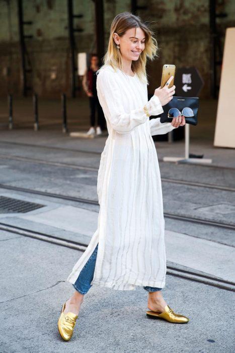 Chica parada en medio de la calle tomándose una fotografía con su celular