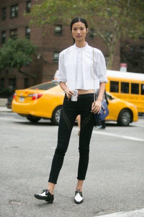 Chica parada en la calle luciendo su outfit y sus zapatos de color blanco con negro estilo mocasines