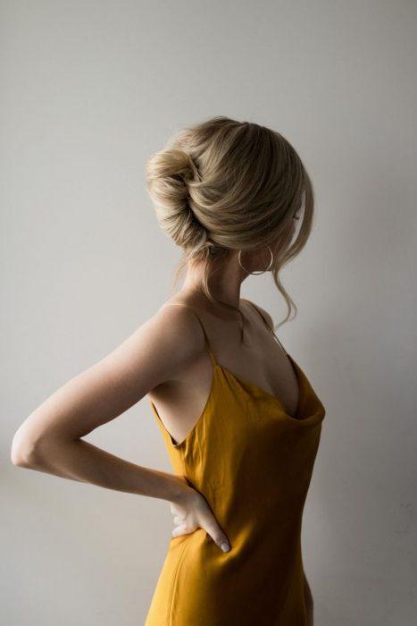 Chica modelando un vestido color amarillo con un peinado de twist francés