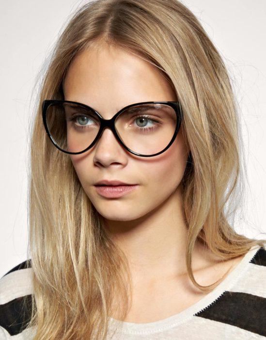 Cara Delevigne mostrandos sus lentes anchos de color negro