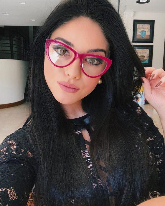 Chica posando para una selfie mientras enseña sus lentes de color rosa