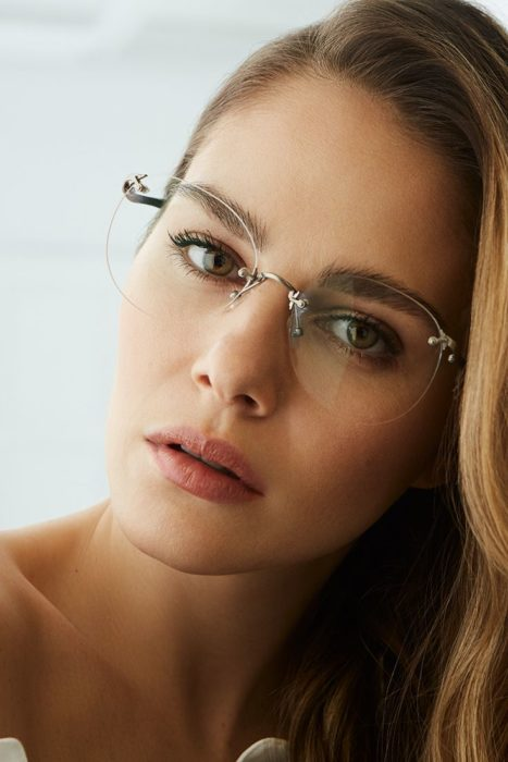 Chica posando para una foto mientras enseña sus pequeños lentes transparentes