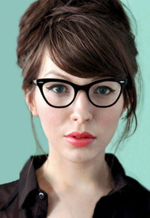 Chica posando para una foto mientras enseña sus pequeños lentes estilo vintage de color negro