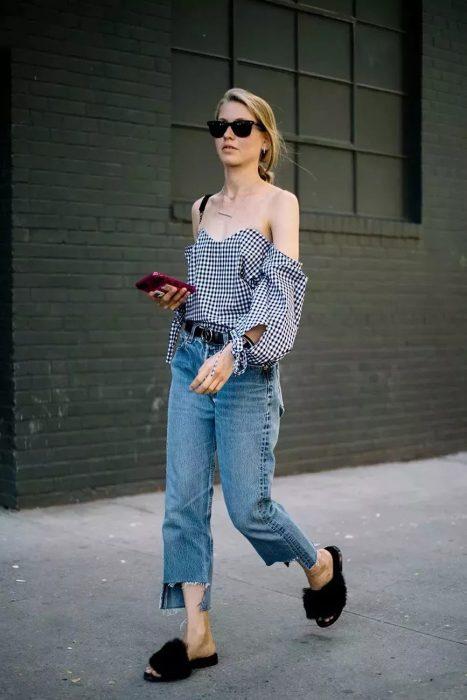 Chica caminando por la calle con el celular en la mano mientras usa jeans, campesina y unas sandalias peludas