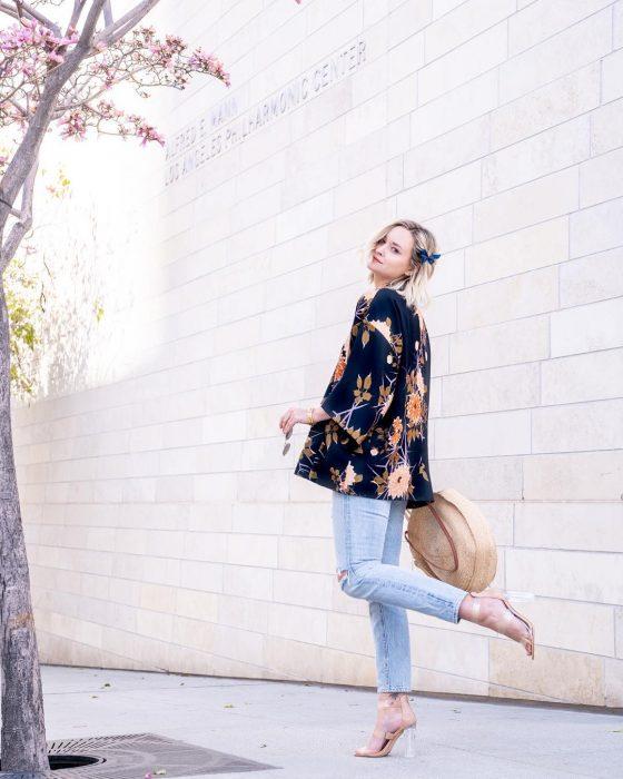 Chica caminando por la calle mostrando sus zapatillas con transparencias, jeans, abrigo y sombrero