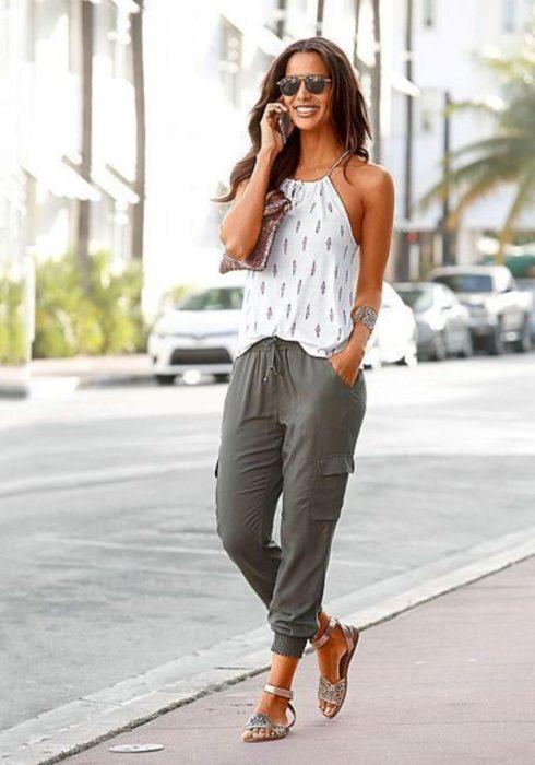 Chica parada en la calle hablando por teléfono y usando jogger de color verde, sandalias, entes y una blusa blanca estampada