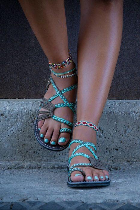 Pies de una chica usando sandalias de correas de color azul aguamarina que combinan con el color de sus uñas