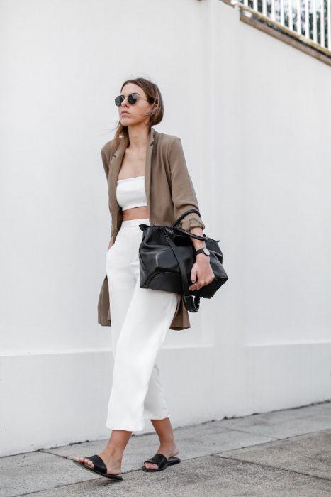 Chica usando un outfit blanco con un cardigan de color café, bolso negro y sandalias de color negro mientras camina por la calle