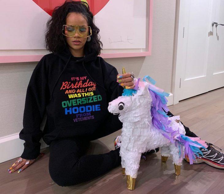 Cantante Rihanna vestida con hoodie grande, negro con letras del color del arcoíris y una piñata de unicornio, tendencia oversized
