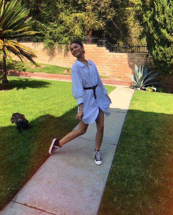 Zendaya modelando en jardín con camisa grande y cinturón negro como vestido, tenis converse, tendencia oversized