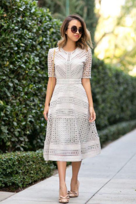 Chica usando un vestido blanco midi tejido mientras camina por la calle