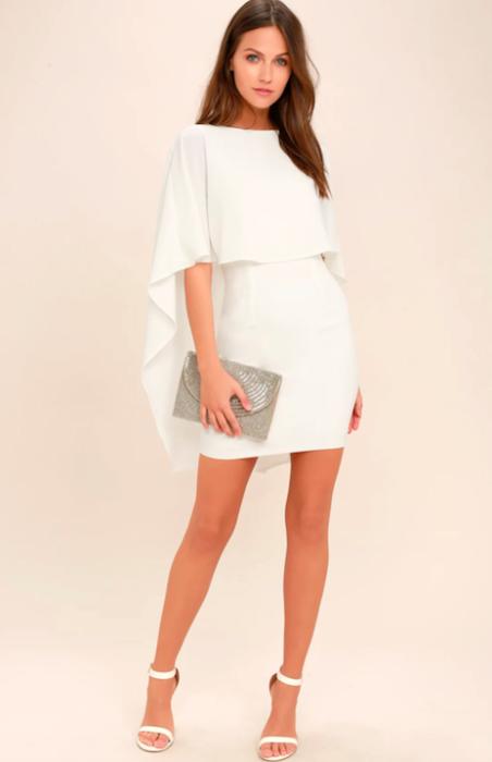 Chica usando un vestido blanco con una pequeña capa mientras sostiene una bolsa en una sesión de fotos