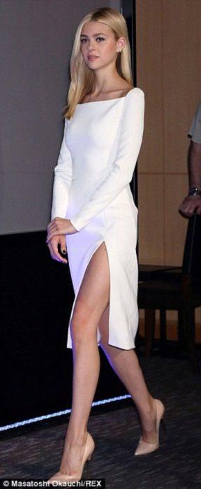 Chica usando un vestido de color blanco hasta la rodilla con mangas y una abertura en una pierna