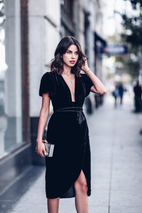 Chica usando un vestido de terciopelo con escote bajo y un cinturón