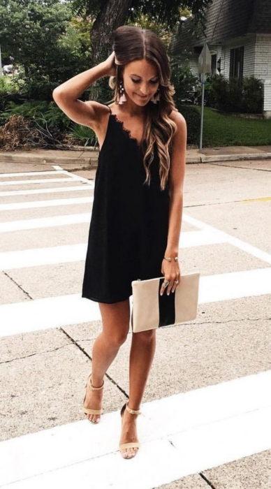 Chica usando un vestido negro estilo bata con sandalias nude y cartera nude