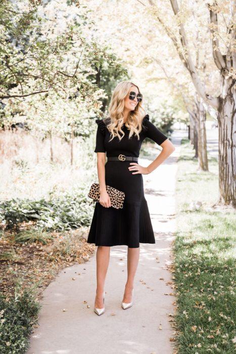 Chica parada en medio de la calle usando un vestido negro con un cinto, tacones dorados y cartera animal print