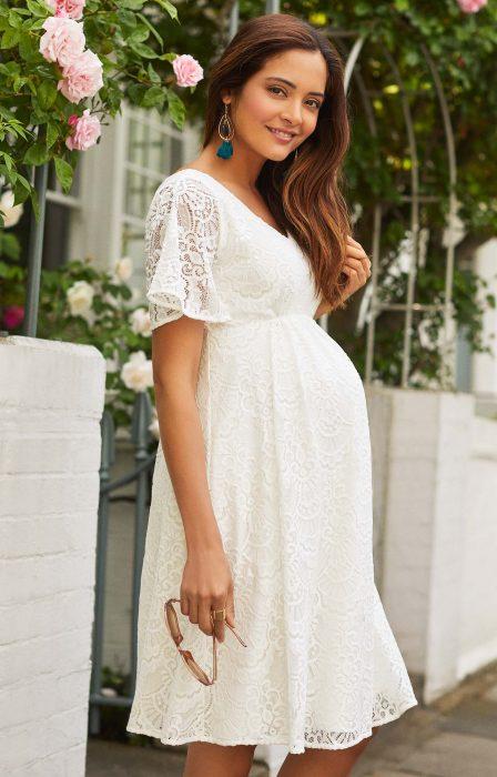 Vestidos para baby shower, mujer de cabello castaño y largo, embarazada con un vestido de encaje corto, blanco y con mangas