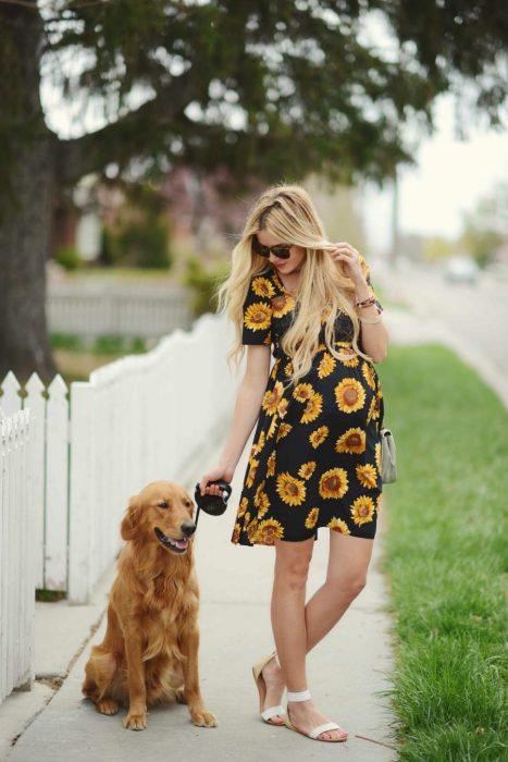 Vestidos para baby shower, mujer de cabello largo y rubio despeinado, paseando a perro golden retriever dorado, con vestido negro con girasoles y sandalias blancas
