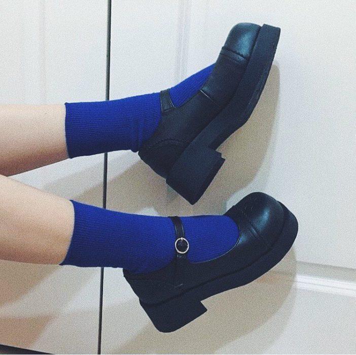 Mujer recostada usando medias azul rey y zapato tipo escolar