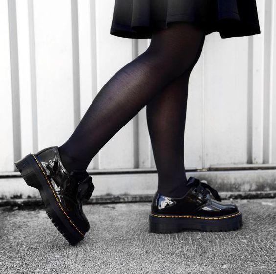 Piernas de mujer con medias negras y zapatos de plataforma ancha