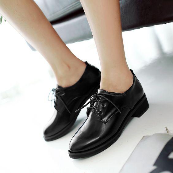 Mujer usando zapatos oscuros, cerrados con tacón bajo