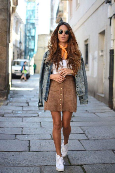 Chica caminando por la calle con falda café, top blanco, chamarra de mezclilla y pañuelo naranja en el cuello