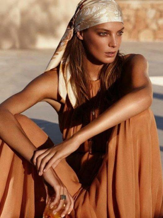 Chica sentada en el pavimento con vestido café y pañuelo en la frente con el cabello suelto
