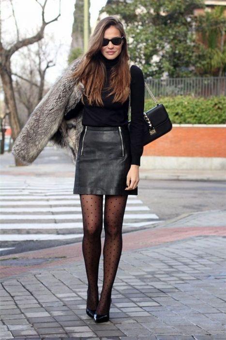 Chica por la calle con falda de piel, suéter negro y stilettos