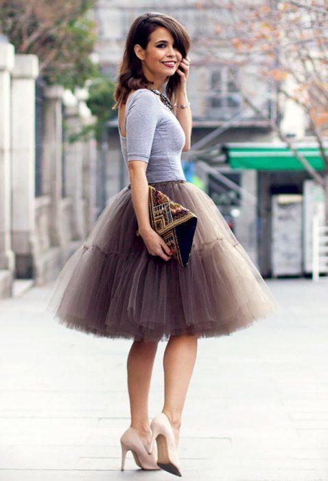 Chica modelando de perfil su falda de tul en color gris verdoso