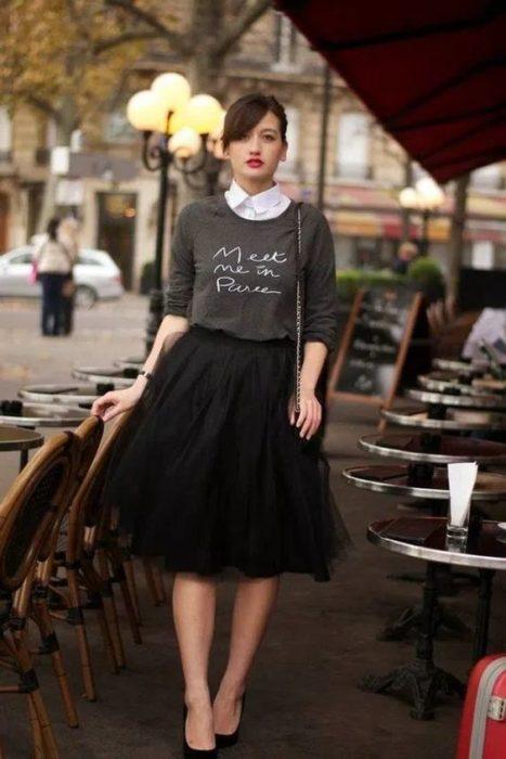 Chica dentro de un café modelando una falsa de tul en negro con sudadera gris claro